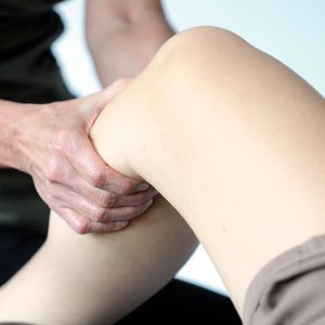 Neuromuscular-therapist-doing-soft-tissue-massage-therapy-on-patient's-leg-muscle-trigger-points-to-relieve-pain